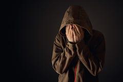 El hombre depresivo en chaqueta con capucha está llorando Imagen de archivo libre de regalías
