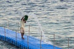 El hombre derrama una corriente grande del agua de un cubo en un Panton en el mediterráneo en la puesta del sol imagenes de archivo