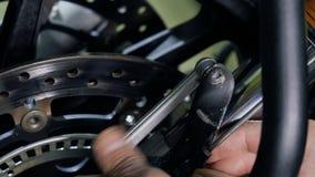 El hombre desatornilla la nuez durante la reparación de la motocicleta almacen de metraje de vídeo