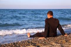 El hombre descalzo en juego de asunto se sienta cómodamente en costa Imagen de archivo libre de regalías