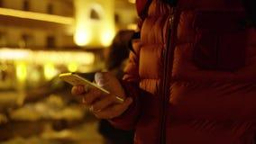 El hombre desconocido en chaqueta roja utiliza su smartphone Tarde del invierno Tirado en c?mara ROJA metrajes