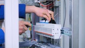El hombre desconocido sujeta las conexiones en la caja del fusible, estante eléctrico Primer 4K almacen de metraje de vídeo