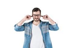 El hombre descontentado que tapa los oídos con el ` t del doesn de los fingeres quiere escuchar fotos de archivo
