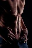 El hombre descubierto muscular con agua cae en el estómago Foto de archivo libre de regalías