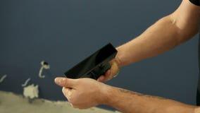 El hombre desempaqueta el paquete, tiradores de puerta negros, considerándolos cuidadosamente almacen de metraje de vídeo