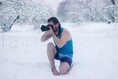 El hombre desnudo con la cámara se sienta en el bosque del invierno Imágenes de archivo libres de regalías