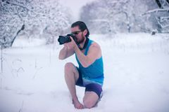 El hombre desnudo con la cámara se sienta en el bosque del invierno Foto de archivo