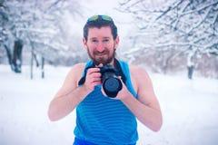 El hombre desnudo hace un poco de foto en el bosque nevoso del invierno Fotografía de archivo