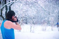 El hombre desnudo hace un poco de foto en el bosque nevoso del invierno Imagenes de archivo