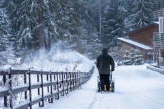 El hombre despeja nieve con el ventilador de nieve Fotografía de archivo libre de regalías