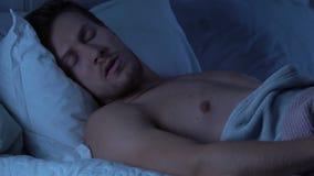 El hombre despierta repentinamente aterrorizado con la pesadilla, día agotador, trastorno del sueño almacen de video