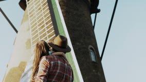 El hombre detiene a la niña en brazos cerca del molino de viento viejo Ángulo bajo de la visión trasera Imagen del padre y del ni metrajes