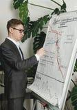 El hombre dibuja diagramms comerciales en el tablero de la presentación del papper fotografía de archivo libre de regalías