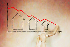 El hombre dibuja el gráfico de la caída de precios de las propiedades inmobiliarias fotos de archivo