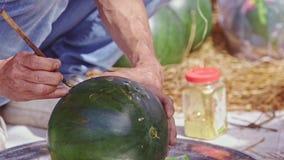 El hombre dibuja la imagen en la sandía en la tabla en Vietnam almacen de video