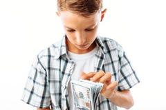 El hombre dijo las cuentas con cientos dólares, el adolescente consiguió su primer dinero ganado en el estudio en un fondo blanco fotografía de archivo libre de regalías