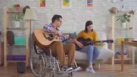 El hombre discapacitado joven en un guitarrista de la silla de ruedas enseña a una muchacha a tocar la guitarra metrajes