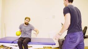 El hombre discapacitado que hace la mano ejercita en el centro de rehabilitación almacen de video