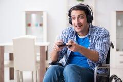 El hombre discapacitado que juega a los juegos de ordenador durante la rehabilitación Fotos de archivo libres de regalías