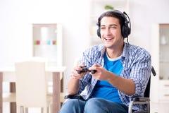 El hombre discapacitado que juega a los juegos de ordenador durante la rehabilitación Foto de archivo