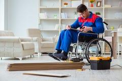 El hombre discapacitado que pone la lamina del piso en oficina imagen de archivo libre de regalías