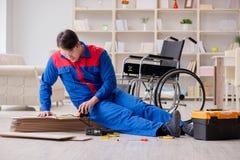 El hombre discapacitado que pone la lamina del piso en oficina imagen de archivo