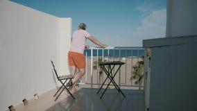 El hombre disfruta de la opinión del mar de una terraza del hotel el vacaciones de verano almacen de video