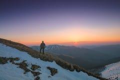 El hombre disfruta de la puesta del sol en las montañas foto de archivo