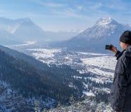 El hombre disfruta de la visión y mira abajo en Garmisch-Partenkirchen y Farchant y toma imágenes con su smartphone Foto de archivo libre de regalías