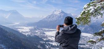 El hombre disfruta de la visión y mira abajo en Garmisch-Partenkirchen y Farchant y toma imágenes con su smartphone Fotos de archivo