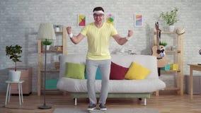 El hombre divertido alegre expresivo en ropa de deportes utiliza escalas del piso metrajes