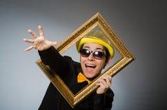 El hombre divertido con el marco Foto de archivo libre de regalías
