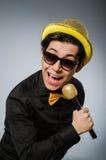 El hombre divertido con el mic en concepto del Karaoke Fotos de archivo