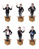 El hombre divertido con las cajas aisladas en blanco Imagenes de archivo