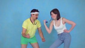 El hombre divertido del coche con el silbido a partir de los años 80 entrenó a una mujer joven con pesas de gimnasia en fondo azu almacen de video