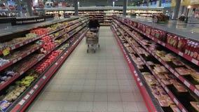 El hombre divertido del comprador corre con el carro en supermercado almacen de video