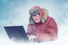 El hombre divertido en invierno viste con el ordenador portátil, frío, nieve imagen de archivo libre de regalías