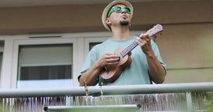 El hombre divertido en un sombrero y gafas de sol juega el ukelele almacen de video