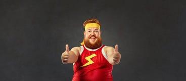 El hombre divertido gordo en ropa de deportes guarda sus fingeres para arriba Imagen de archivo libre de regalías