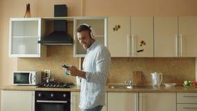 El hombre divertido joven hermoso en los auriculares que bailan y que cantan en cocina en casa por la mañana y se divierte el vac almacen de metraje de vídeo