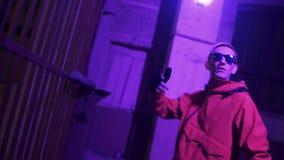 El hombre divertido vestido en ropa y gafas de sol rojas del deporte canta activamente en la noche almacen de metraje de vídeo