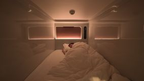 El hombre duerme dentro de una habitación moderna limpia de cápsula con las luces y el aircon metrajes