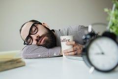 El hombre duerme en oficina en la tabla sobre el ordenador portátil con café a disposición Fotografía de archivo libre de regalías