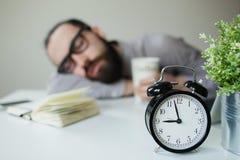 El hombre duerme en oficina en la tabla sobre el ordenador portátil con café a disposición Fotos de archivo libres de regalías