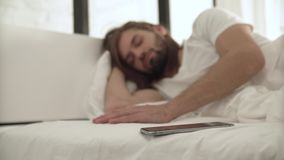 El hombre durmiente despierta en cama por llamada en el teléfono móvil almacen de metraje de vídeo