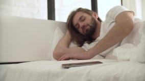 El hombre durmiente despierta en cama por llamada en el teléfono móvil metrajes
