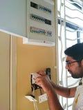El hombre eléctrico instala el enchufe de la cubierta Foto de archivo