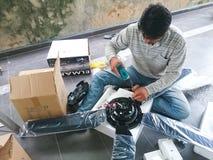 El hombre eléctrico instala una fan de techo Imagen de archivo