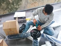 El hombre eléctrico instala una fan de techo Fotografía de archivo
