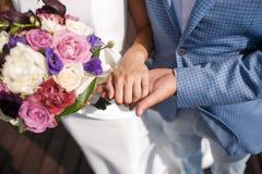 El hombre el novio guarda la mano del ` s de la muchacha Ramo nupcial colorido día de boda, accesorios de la novia Fotos de archivo